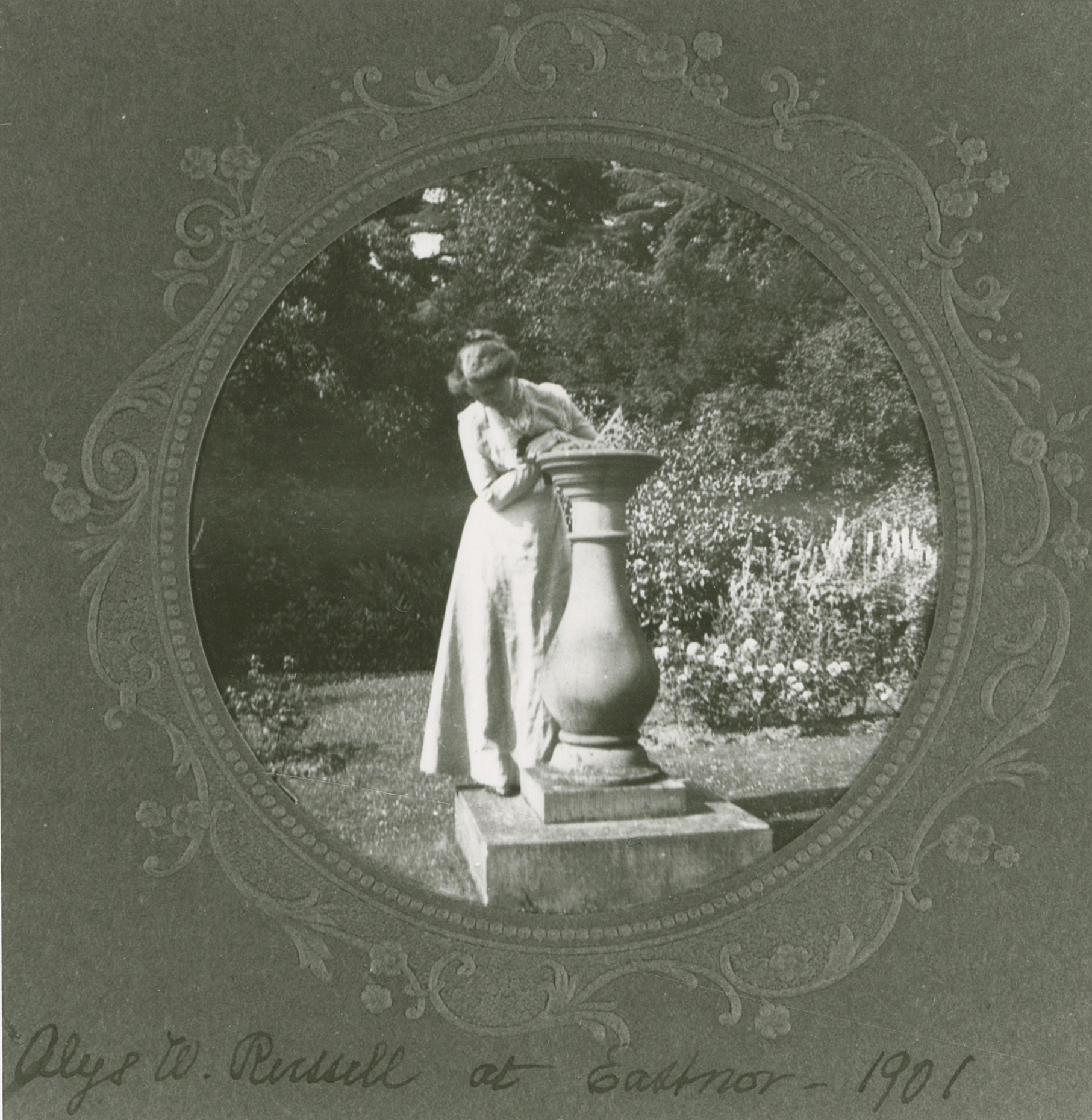 White woman leaning against a large planter in a garden.