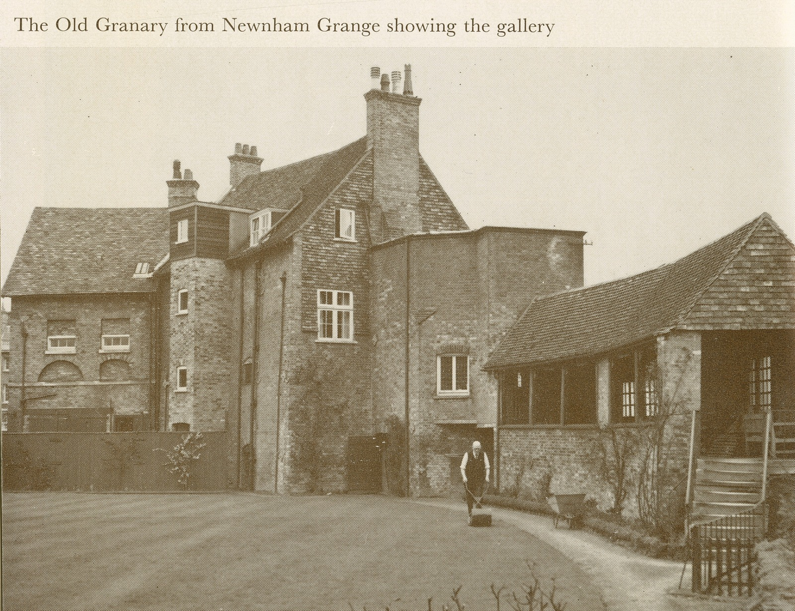 Greyscale image of brick or stone granary from the Grange, with person doing lawn work