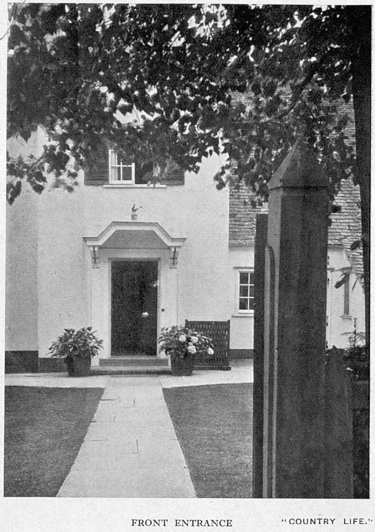 Black and white photo looking along path to front door of house.