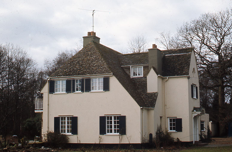 Colour photo of two storey white house from side
