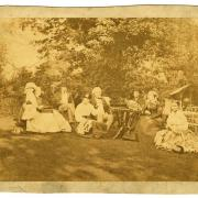 Sepia toned photograph of family sitting outside in clothing from the mid-late 1800s.