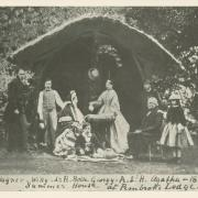 Black and white image of family in late 1800s dress outside thatched roof summer home.