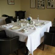 Table set for formal tea with armchairs.