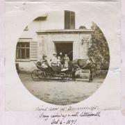 Black and white photograph of a family in a carriage in front of a house.