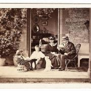 Black and white photograph of a family sitting on terrace with dog.