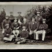 Group of rowers sit for team photo in Victorian garb