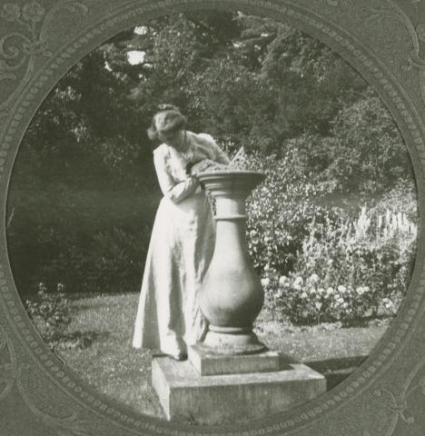 White woman in a long dress leaning on a large urn in a garden.