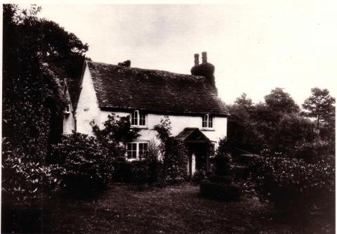 Black and white image of two-storey, white brick cottage amidst trees and garden.