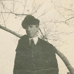 Bertrand Russell in winter coat and hat with tree in background.